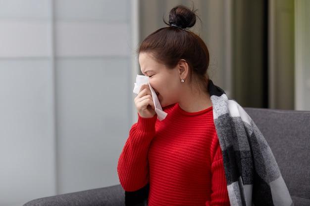 Horizontaal schot van donkerharige jonge vrouw heeft griep, niest in zakdoek, heeft lopende neus, gekleed in warme gebreide rode trui, koud gevangen in de winter. mensen, ziekte en infectie concept.