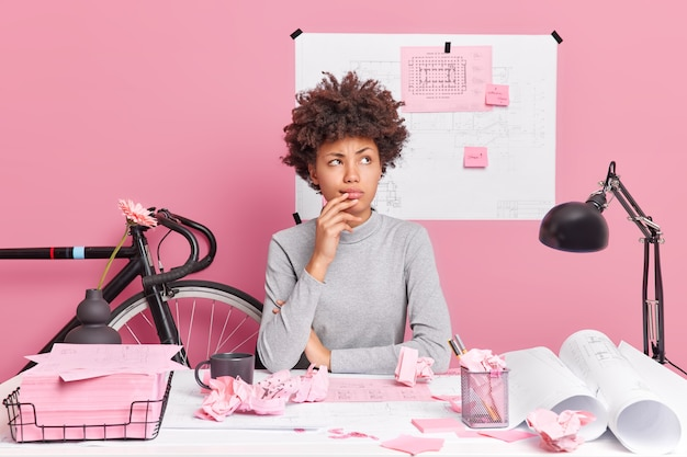 Horizontaal schot van doordachte afro-amerikaanse vrouw poseert in coworking-ruimte heeft peinzende uitdrukking maakt architecturaal project trekt schetsen voor het ontwerpen van nieuw gebouw maakt planningen of veronderstellingen