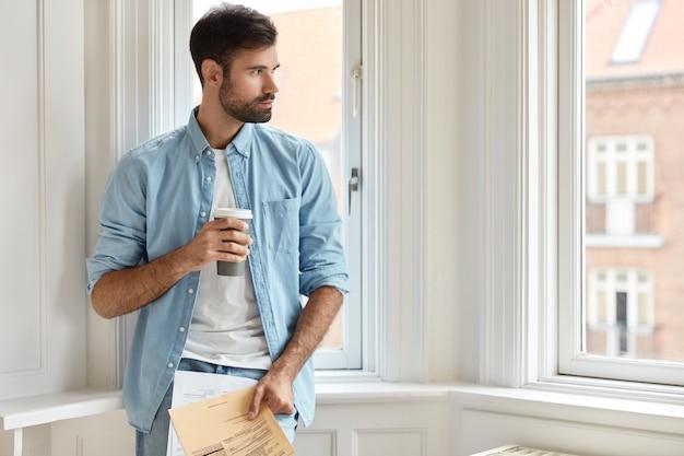 Horizontaal schot van doordachte bebaarde man thuis werken