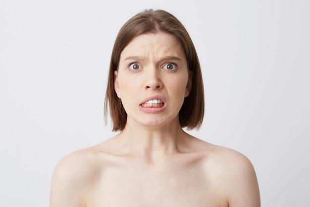 Horizontaal schot van droevige ongerust gemaakte jonge vrouw met perfecte huid