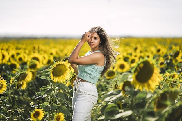 Horizontaal schot van een blanke jonge vrouw poseren in een helder veld met zonnebloemen op een zonnige dag