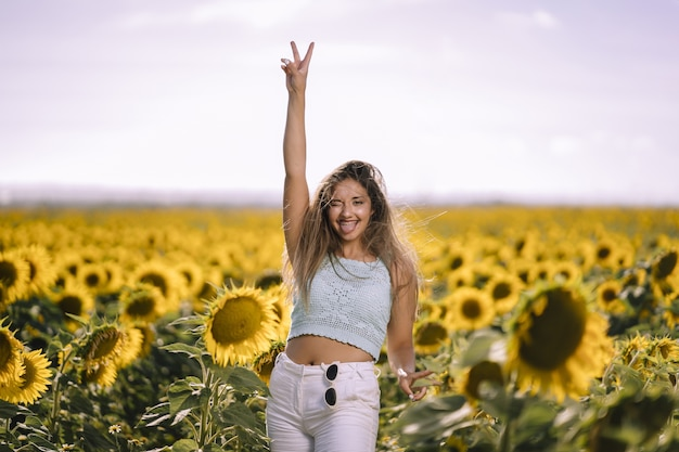 Horizontaal schot van een blanke jonge vrouw poseren in een helder veld met zonnebloemen op zonnige dag