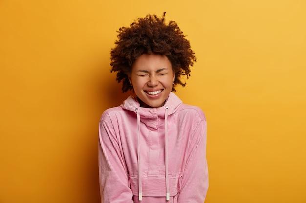 Horizontaal schot van een donkere jonge vrouw die lacht om iets grappigs, giechelt over een hilarische grap, verheugt zich over een positieve gebeurtenis, draag een roze hoodie, modellen binnen. mensen, geluk, levensstijlconcept