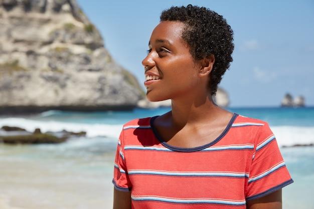 Horizontaal schot van een donkere tiener met kort krullend haar