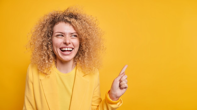 Horizontaal schot van een gelukkige vrouw met krullend haar die tandjes glimlacht, geeft aanbeveling