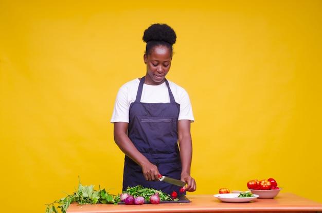 Horizontaal schot van een jonge, aantrekkelijke afrikaanse kok die groenten snijdt met een mes