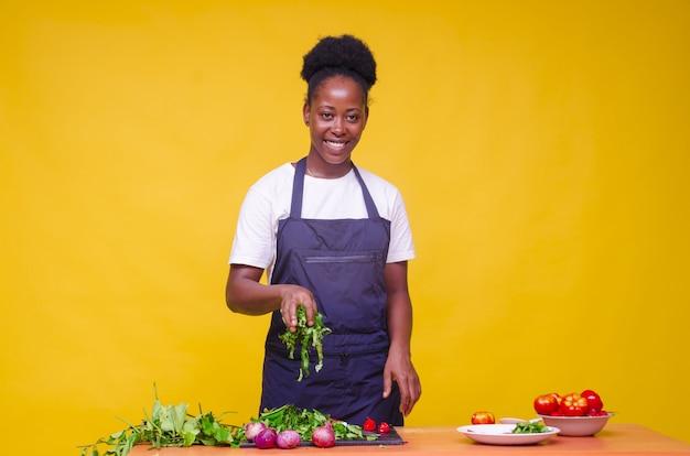 Horizontaal schot van een jonge, aantrekkelijke afrikaanse kok met groen/oranje muur