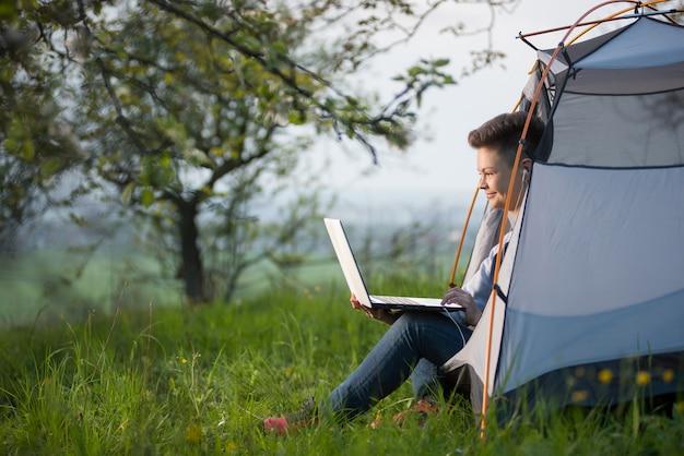 Horizontaal schot van een jonge vrouw die in openlucht in een tent kampeert die haar laptop met behulp van
