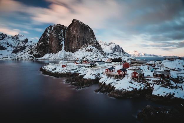 Horizontaal schot van een kuststad met rode huizen dichtbij een overzees en een sneeuwberg in de rug