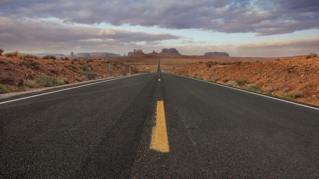 Horizontaal schot van een lege weg in monument valley, de vs met de achtergrond van adembenemende hemel