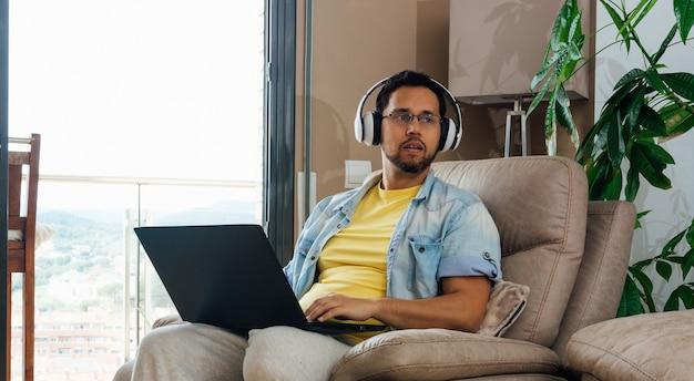 Horizontaal schot van een mannetje dat aan muziek met hoofdtelefoons en laptop op knieën luistert