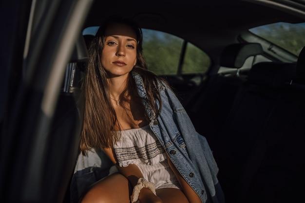 Horizontaal schot van een mooie jonge blanke vrouw die zich voordeed op de achterbank van een auto in een veld