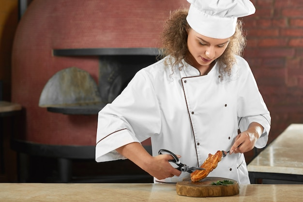 Horizontaal schot van een mooie vrouwelijke chef-kok die bij het restaurantkeuken snijden die geroosterd vlees snijden met de baanberoepswerknemer van het schaar copyspace beroep.