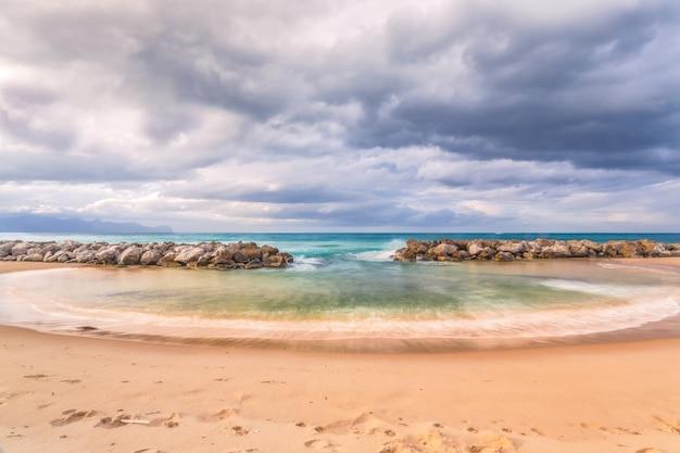 Horizontaal schot van een prachtig strand met rotsen onder de adembenemende bewolkte hemel