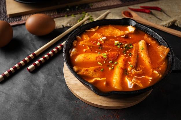Horizontaal schot van een soep in zwarte kom en enkele eieren en houten eetstokjes