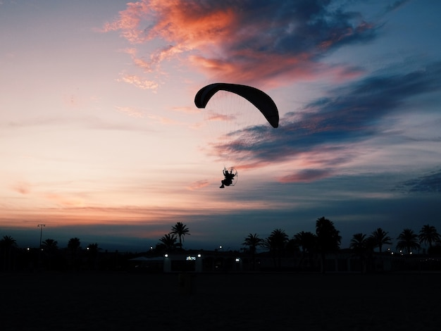 Horizontaal schot van een strand met een persoon die op een paramotorische parachute naar beneden glijdt