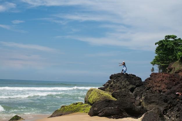Horizontaal schot van een vrouw met een hoed en blauwe jurk op een rotsachtig strand