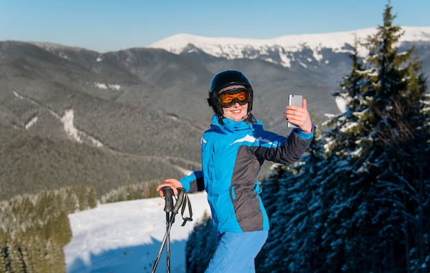 Horizontaal schot van een vrouwelijke skiër die glimlachend gebruikend haar slimme telefoon die foto's neemt