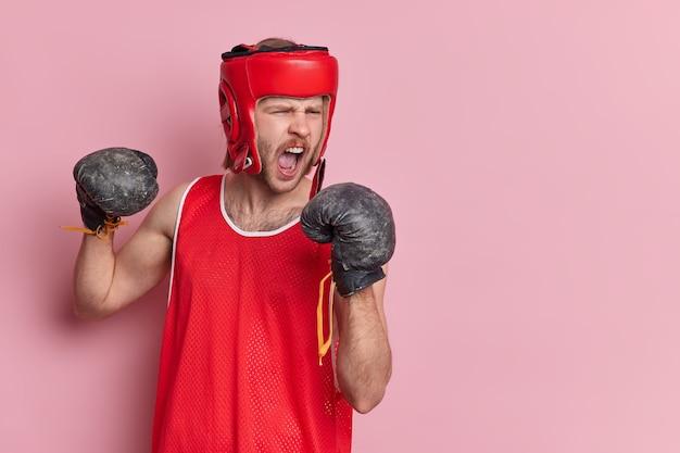 Horizontaal schot van emotionele ongeschoren mannelijke bokser roept luid mond open