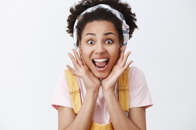Horizontaal schot van emotionele opgewonden schattige afro-amerikaanse vrouw in hoofdband en gele zomeroverall, palmen in de buurt van gezicht en breed glimlachend, concert van favoriete band bezoeken, opgewonden voelen