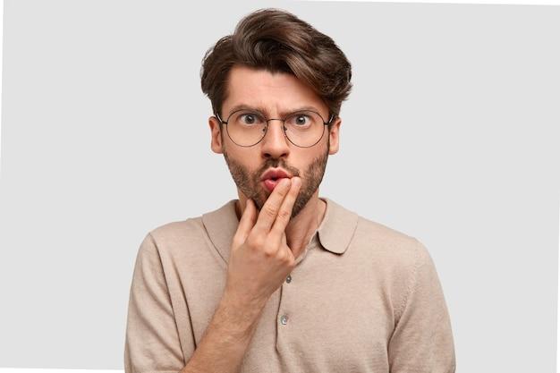 Horizontaal schot van emotionele verbaasde boze europese man houdt kin en kijkt verbijsterd, heeft ernstige uitdrukking