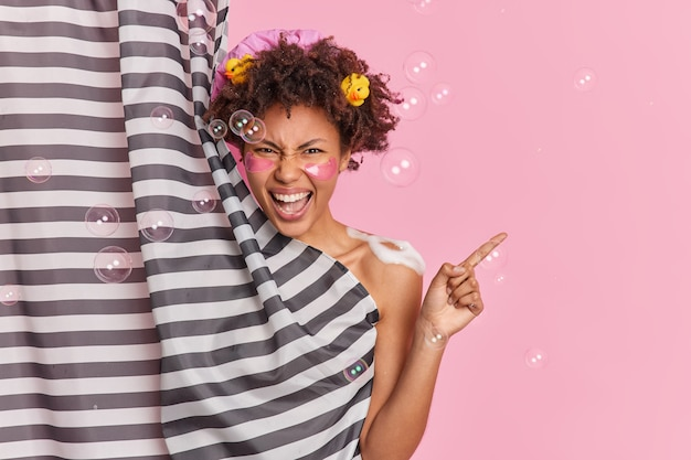 Horizontaal schot van emotionele vrouw neemt douche geldt schoonheid pads onder ogen schreeuwt boos wijst weg op lege ruimte voor uw advertentie-inhoud