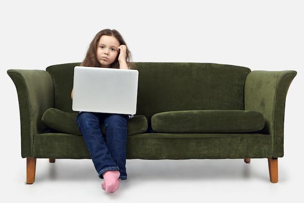 Horizontaal schot van ernstige doordachte 10-jarige europese meisje zittend op de bank in de woonkamer, gezicht krabben, camera kijken met peinzende verwarde uitdrukking.