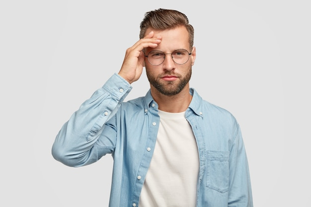 Horizontaal schot van ernstige ongeschoren man heeft peinzende uitdrukking, houdt de hand op het voorhoofd, probeert te verzamelen met gedachten, gekleed in een blauw shirt, intelligent te zijn, geïsoleerd over witte muur
