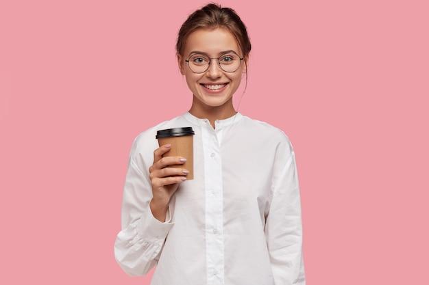 Horizontaal schot van gelukkig kaukasisch meisje in wit overhemd, draagt papieren beker met koffie, stel voor om te drinken