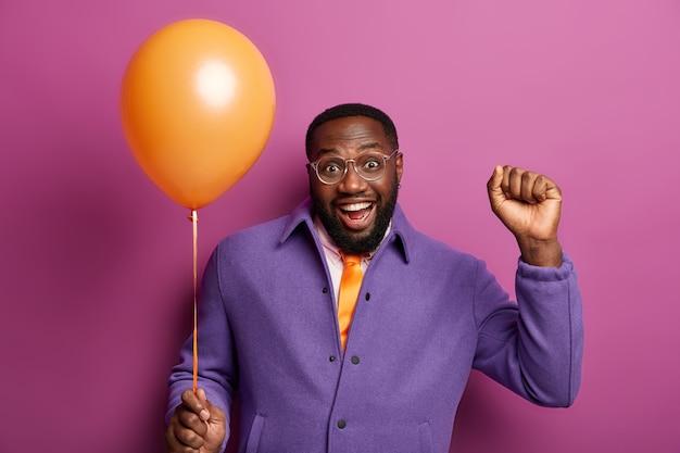 Horizontaal schot van gelukkig zwarte man viert succesvolle afwerking van de universiteit of hogeschool