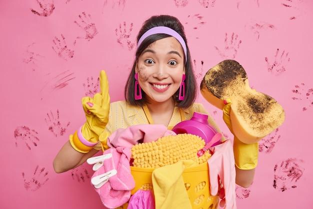 Horizontaal schot van gelukkige aziatische vrouw glimlacht aangenaam houdt vinger omhoog toont resultaten van haar werk houdt spons verzamelt wasgoed in mand poses tegen roze muur