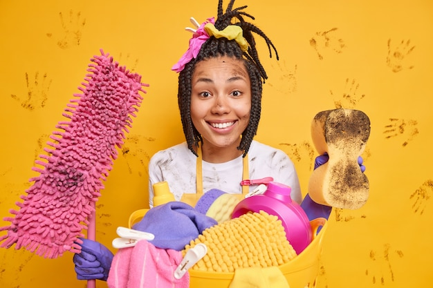Horizontaal schot van gelukkige huishoudster glimlacht aangenaam in een goed humeur na het schoonmaken van appartement poses in de buurt van wasmand geïsoleerd over gele muur