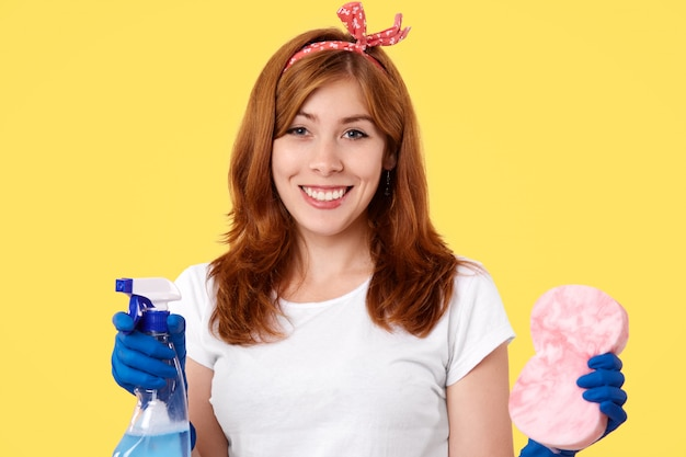 Horizontaal schot van gelukkige huisvrouw draagt casual t-shirt en hoofdband, roodachtig om huis schoon te maken, houdt spray voor wirndows en spons