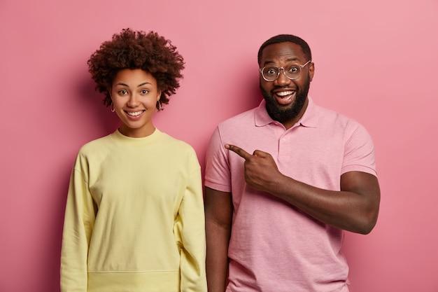 Horizontaal schot van gelukkige man in roze t-shirt wijst naar vriendin, heeft een positieve uitstraling