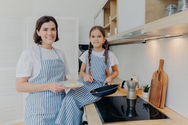 Horizontaal schot van gelukkige moeder en klein vrouwelijk meisje, bezig het voorbereiden van gebraden eieren voor ontbijt of diner