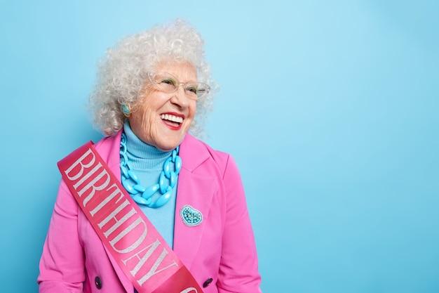 Horizontaal schot van gelukkige oude vrouw viert jubileum blij met felicitaties gekleed in feestelijk kledinglint met geschreven woord verjaardag heeft een goed humeur