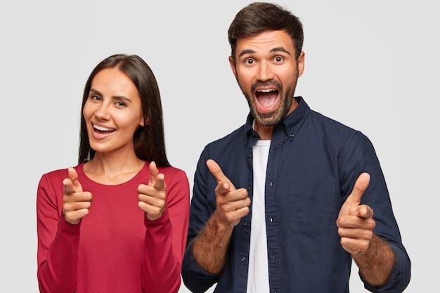 Horizontaal schot van gelukkige vrienden wijzen vingers naar u, gebaar binnen, maak keuze, hebben positieve uitdrukkingen