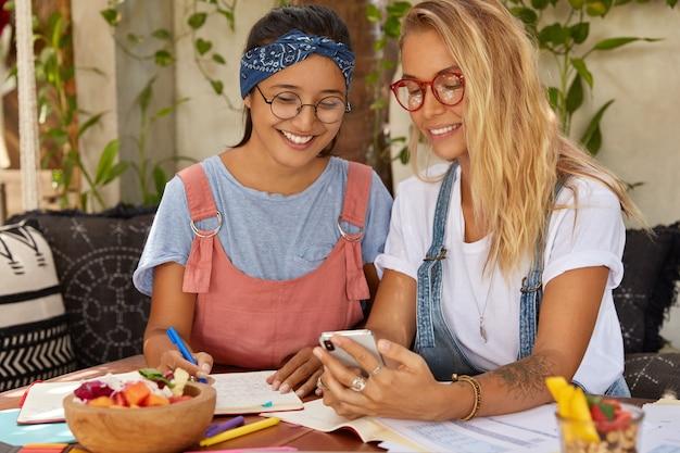 Horizontaal schot van gelukkige vrouwen bespreken grappige blog op internet, gebruik mobiele telefoon