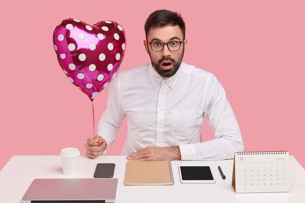 Horizontaal schot van geschokt ongeschoren jong mannetje in wit formeel overhemd, draagt valentijnskaart voor vriendin, verrast haar met minnaar op te merken