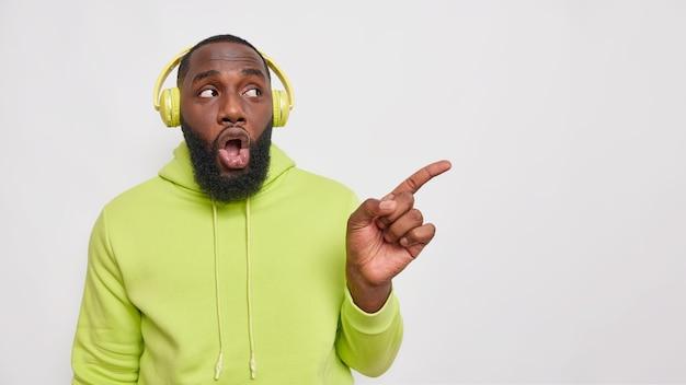 Horizontaal schot van geschokte bebaarde man met donkere huid luistert audiotrack via draadloze koptelefoon draagt groene sweatshirt wijst weg op lege ruimte geïsoleerd over witte muur