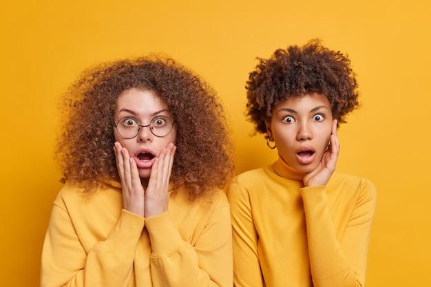 Horizontaal schot van geschokte, geschrokken vrouwen van gemengd ras die hun mond openen van grote verbazing en ontdekken dat verrassende onthulling angstig geïsoleerd over gele achtergrondkleur is. menselijke reacties concept