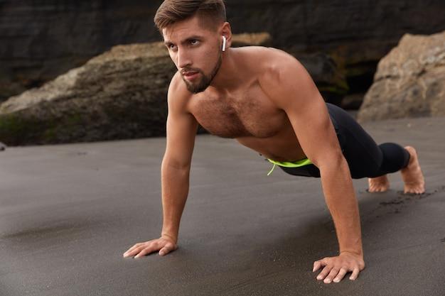 Horizontaal schot van gespierde jonge sportman of atleet doet plankpositie, geniet van frisse zeelucht