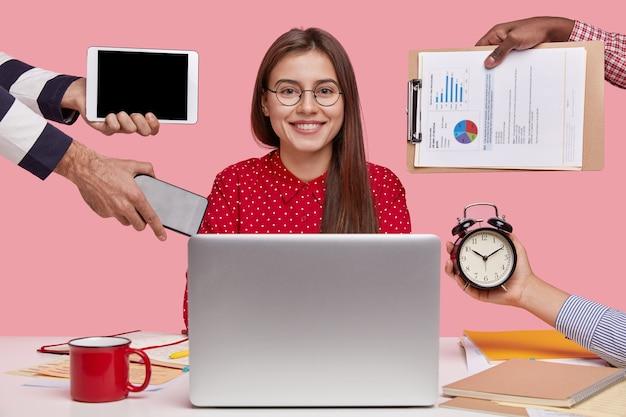 Horizontaal schot van glimlachende mooie vrouw in rood overhemd, zit voor geopende laptop computer
