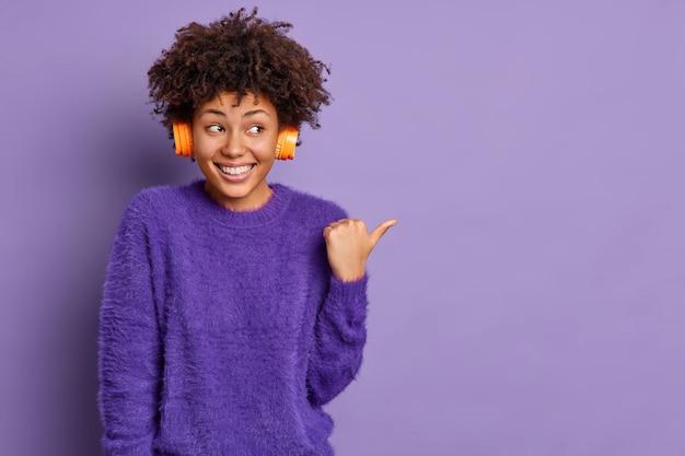 Horizontaal schot van goed uitziende vrolijke afro-amerikaanse vrouw luistert audiotrack wijst duim weg op lege ruimte glimlach positief poses