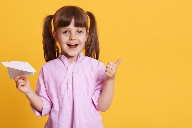 Horizontaal schot van grappig vrolijk kind dat gebaar maakt, duim omhoog, goedkeuring toont, vliegtuig houdt, paardenstaarten heeft, alleen zijn. copyspace voor reclame.