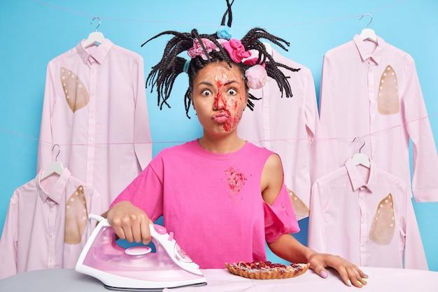 Horizontaal schot van grappige huisvrouw bezig met dagelijkse huishoudelijke klusjes koks taart strijkijzers wasgoed vuil na huishoudelijk werk poses tegen gestreken verbrande shirts hangend aan touw over blauwe muur
