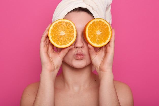 Horizontaal schot van grappige vrolijke jonge vrouw die twee helften sinaasappel tegen haar ogen houdt, die witte handdoek op haar hoofd heeft, die met blote schouders over rooskleurige muur stelt. schoonheid concept.