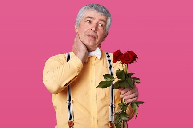 Horizontaal schot van grijze haired oudere man in formele modieuze kleding, houdt de hand op de nek, heeft pijn, kijkt opzij, houdt rode rozen