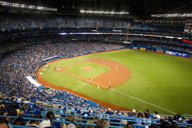 Horizontaal schot van het drukke honkbalstadion van yankee en spelers in het veld