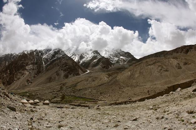 Horizontaal schot van hoge stijgings rotsachtige bergen dichtbij de karakoram-weg in china dat in sneeuw wordt behandeld